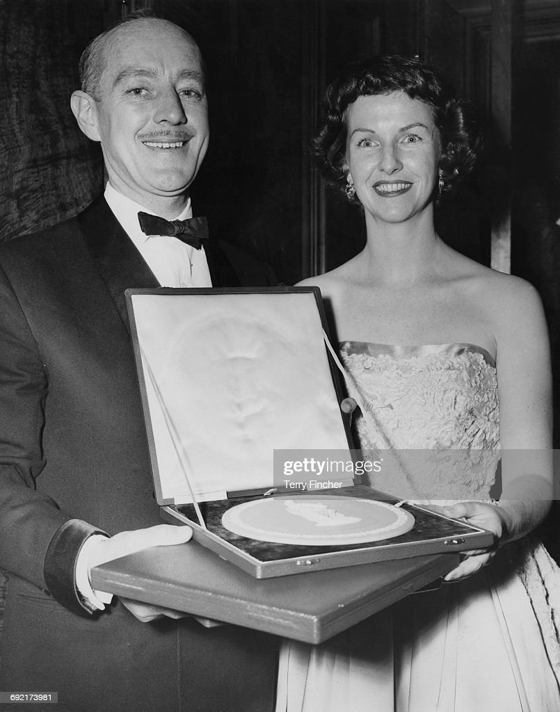 English actor Alec Guinness (1914 - 2000) holding the award he has accepted on behalf of actress Katie Johnson for her role in 'The Ladykillers', at the British Academy Film Awards at the Odeon, Leicester Square, 1st March 1956. Next to him is actress Betsy Blair (1923 - 2009), winner of the Best Foreign Actress award for her role in 'Marty'.