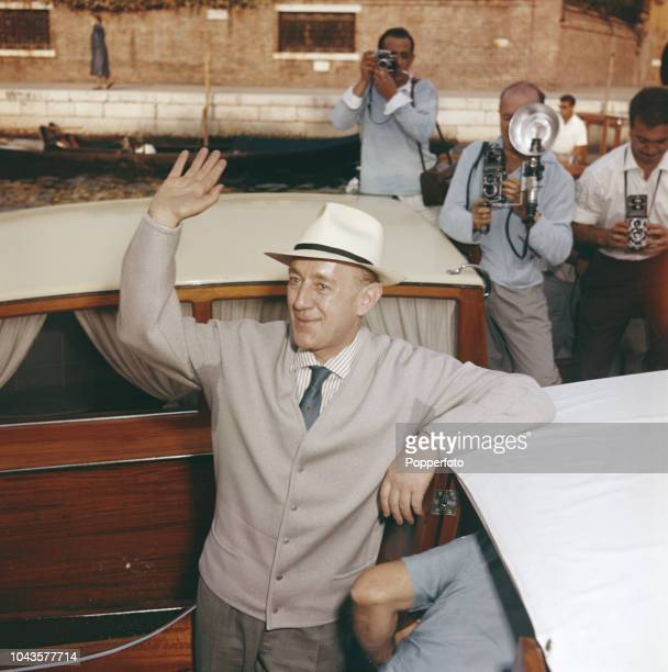 English actor Alec Guinness waves to onlookers from a boat on a canal during the 1960 Venice International Film Festival in Venice Italy in September...