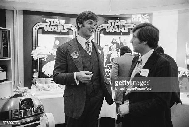 English actor and bodybuilder David Prowse stands in front of the Star Wars merchandise stand at the Birmingham toy fair on 13th January 1978 Dave...