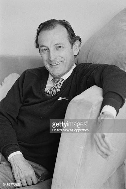 English actor and broadcaster Gerald Harper pictured sitting on a sofa in London on 29th April 1983