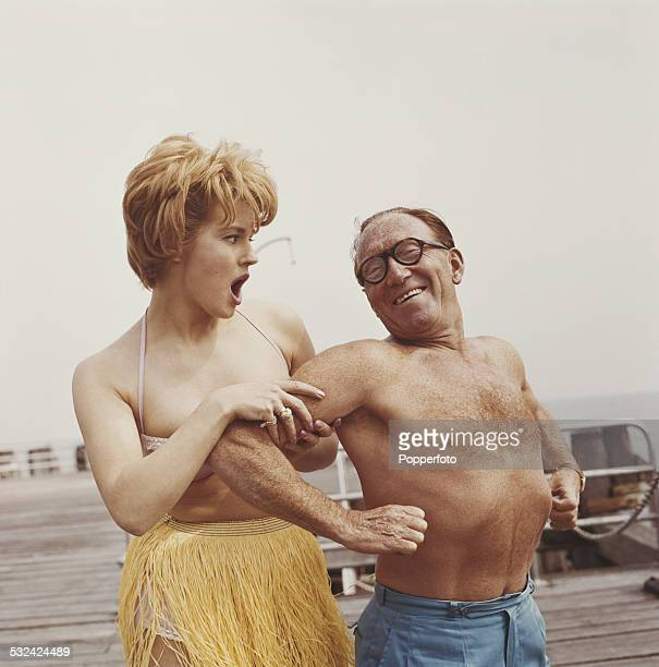English actor and comedian Arthur Askey pictured bare chested with a young girl wearing a bikini and grass hula skirt holding his arm at Southsea in...