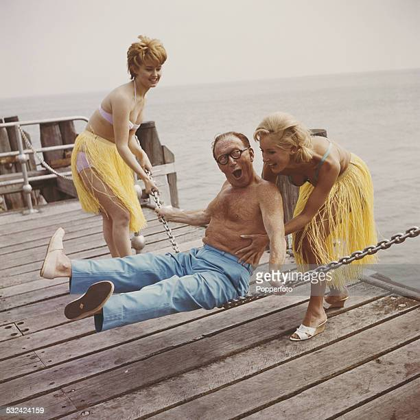 English actor and comedian Arthur Askey pictured bare chested with two young girls wearing bikinis and grass hula skirts swinging him on a metal...