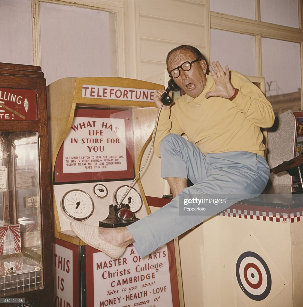 English actor and comedian, Arthur Askey (1900-1982) pictured listening to a fortune telling machine in an amusement arcade at Southsea in England in 1963.