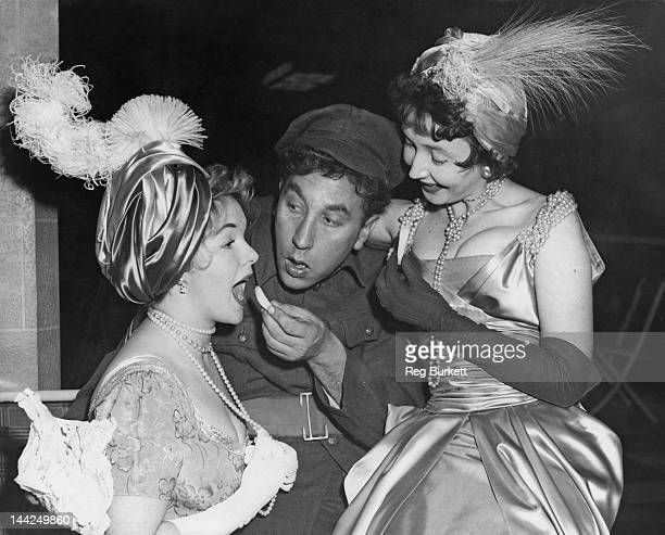 English actor and comedian Frankie Howerd helps to make up actresses Peggy Cummins and Dulcie Gray during rehearsals for the Royal Variety...
