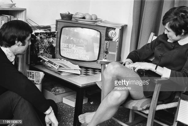 English actor and comedian Michael Palin and his wife Helen Gibbins watch a broadcast of an episode of 'Do Not Adjust Your Set' in London in February...