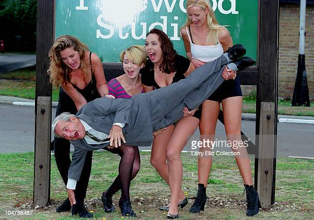 English actor and comedian Norman Wisdom gets a lift from a group of young ladies at Pinewood Studios during a photoshoot for the film 'Adam and...