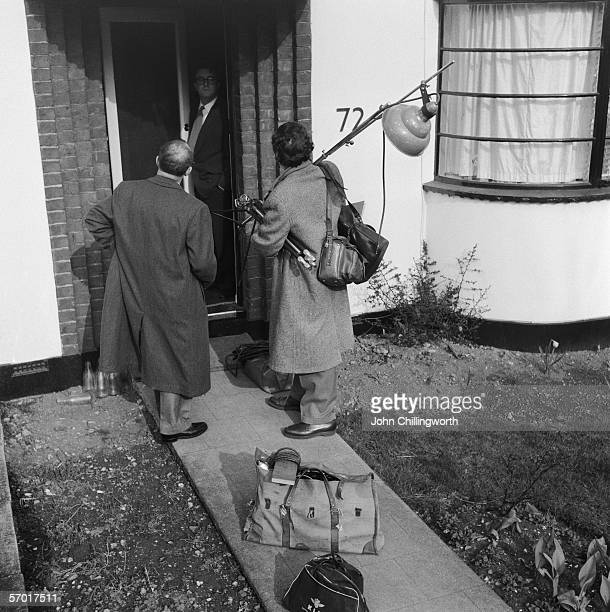 English actor and comedian Peter Sellers answers the door at his Muswell Hill home to Picture Post journalist Bob Muller and photographer Thurston...