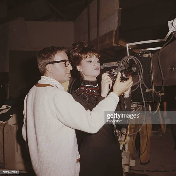 English actor and comedian Peter Sellers demonstrates the settings on a singlelens reflex camera to American singer Fran Jeffries on the set of the...