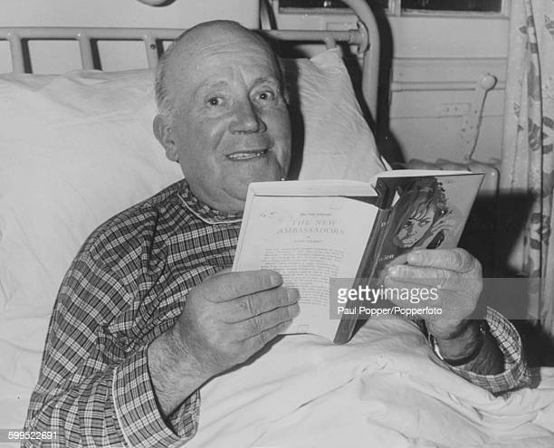English actor and comedian Wally Patch pictured reading a book in his hospital bed where he is recuperating from a heart and lung complaint at New...