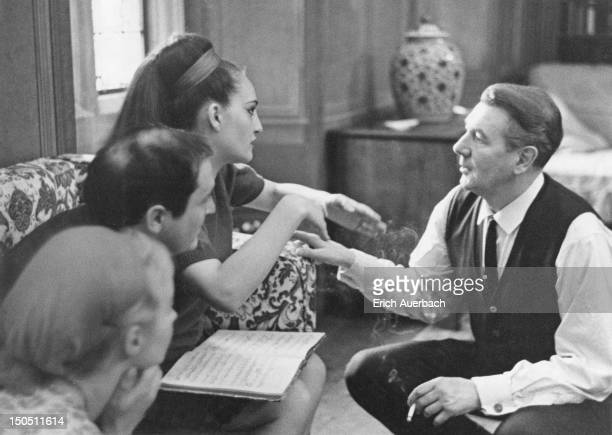 English actor and director Sir Michael Redgrave talking to operatic soprano Helia T'Hezan in the Organ Room at Glyndebourne, East Sussex, 8th May...