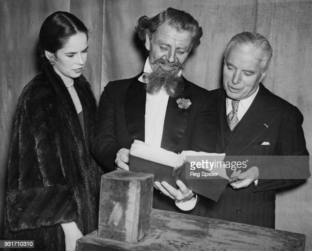 English actor and filmmaker Charlie Chaplin and his wife Oona visit actor Emlyn Williams on the stage of the Ambassador's Theatre in London where...