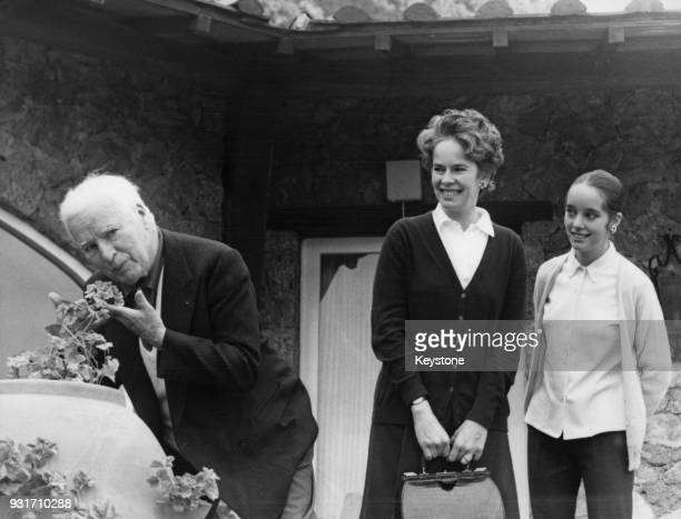 English actor and filmmaker Charlie Chaplin sniffs the geraniums at the Villa Scala dei Santi during a holiday in Porto Ercole Italy watched by his...