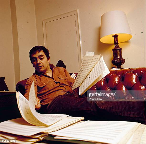 English actor and musician Dudley Moore lies on a leather Chesterfield style sofa leafing through sheets of a musical score in 1966