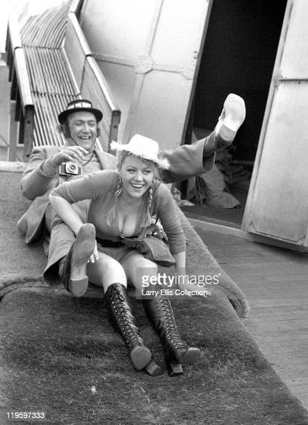 English actor Bernard Bresslaw enjoys himself on Brighton Pier with glamour model and actress Margaret Nolan during the filming of 'Carry On at Your...