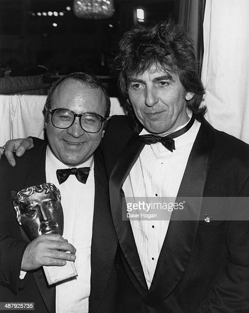 English actor Bob Hoskins with George Harrison of the Beatles at the BAFTA awards London UK 22nd March 1987 Hoskins won the Best Actor award for his...