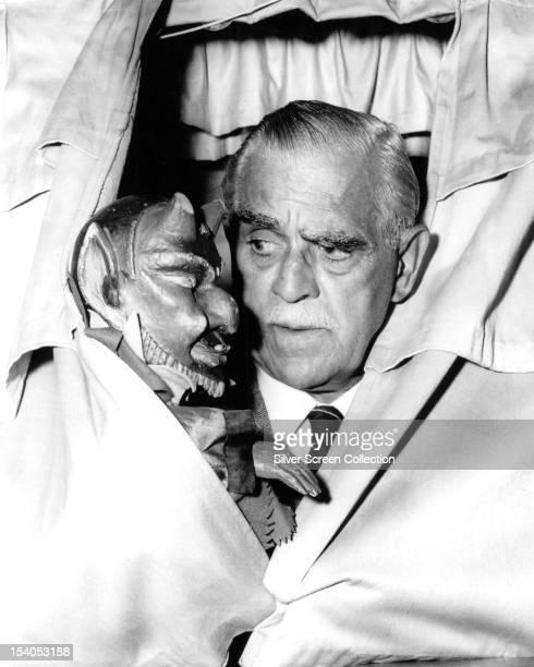 English actor Boris Karloff with a devil puppet, circa 1960.