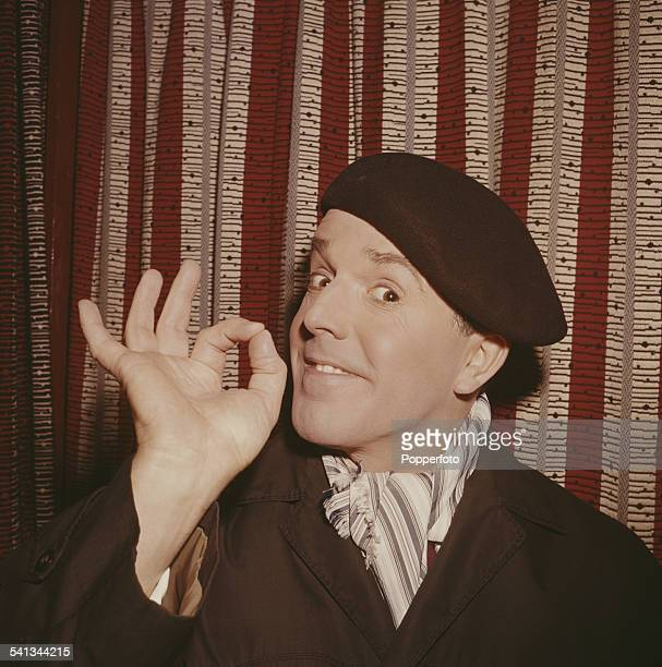 English actor Brian Rix pictured wearing a beret scarf and mac in 1962
