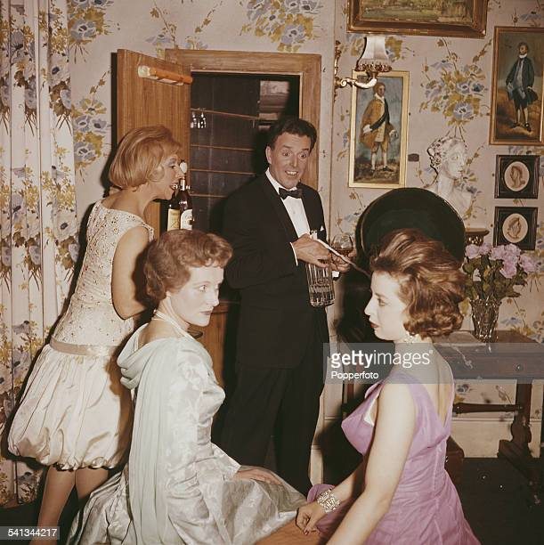 English actor Brian Rix pictured with three actresses including Helen Jessop weaing a pink dress in a scene from the play 'One for the Pot' in 1962