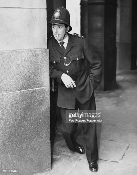 English actor Brian Rix wearing police uniform playing the character of PC Percy Hobson smoking a cigarette during rehearsals for the BBC show 'A...