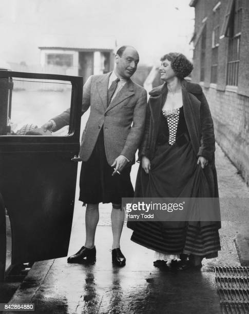 English actor Cedric Hardwicke and actress Anna Neagle leaving the set of the film 'Nell Gwynn' at Elstree Studios whilst still partially costumed as...