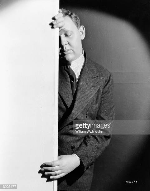 English actor Charles Laughton half obscured by a wall and with his eyes closed in thought