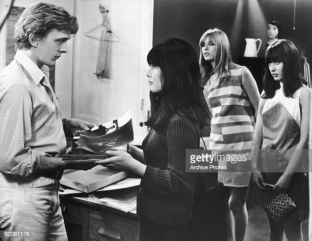 English actor David Hemmings stars as a photographer in the film 'Blowup' 1966 Here he is visited by two female fans whilst talking to his...
