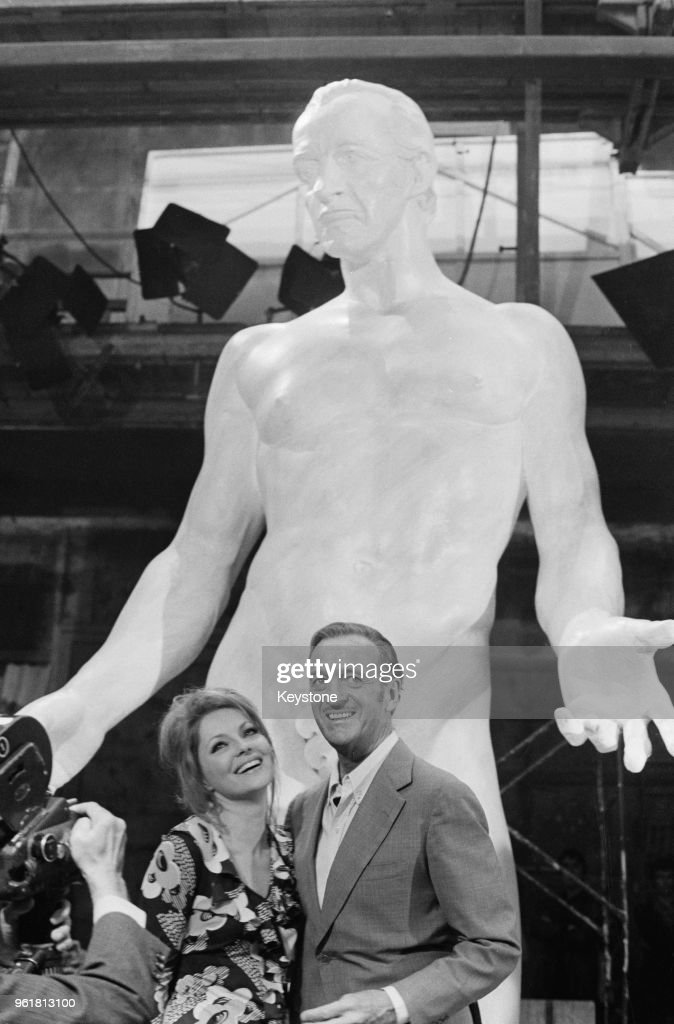English actor David Niven (1910 - 1983) unveils an 18-foot nude statue of himself at the Cinecitta studios in Rome, assisted by actress Virna Lisi (1936 - 2014), 20th May 1970. The statue is a prop for the film 'The Statue', in which they both star.