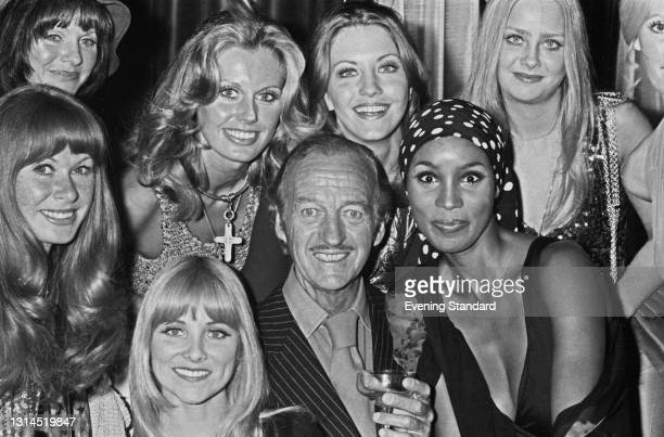 English actor David Niven with a group of female co-stars from his upcoming film 'Old Dracula', aka 'Vampira', UK, 23rd July 1973. Pictured with...
