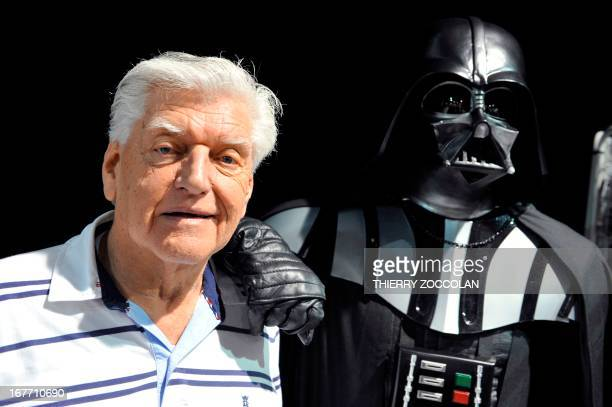 English actor David Prowse who played the character of Darth Vader in the first Star Wars trilogy poses with a fan dressed up in a Darth Vader...