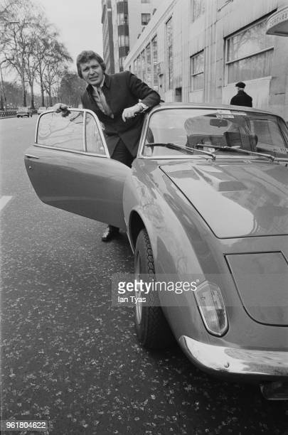 English actor Derren Nesbitt emerges from his new red Lotus 2 Plus 2 outside the Dorchester Hotel in London, 1971.