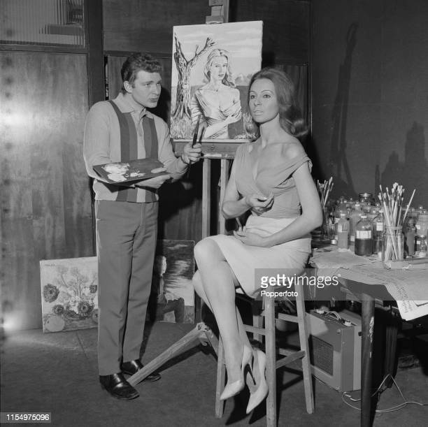 English actor Derren Nesbitt pictured painting a portrait in oils of his wife actress Anne Aubrey at home in March 1965