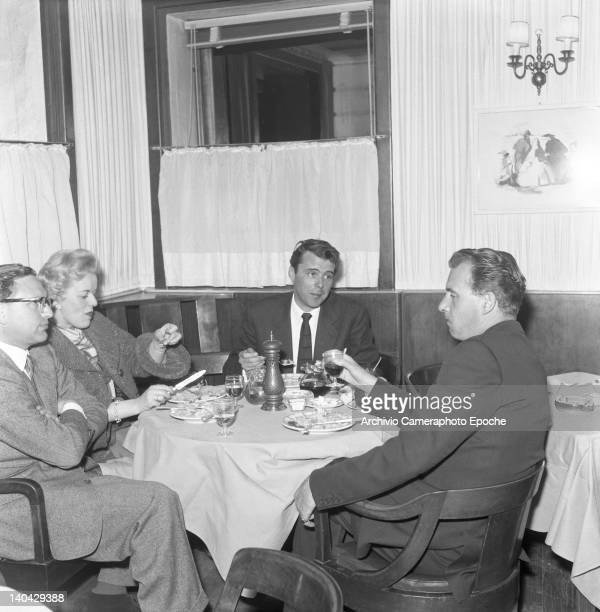 English actor Dirk Bogarde eating at the restaurant with the producer Betty Box and Ralph Thomas Lido Venice 1957