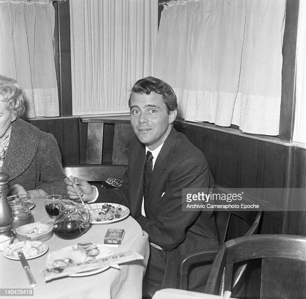 English actor Dirk Bogarde eating at the restaurant with the producer Betty Box Lido Venice 1957