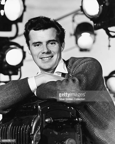 English actor Dirk Bogarde leaning on a movie camera circa 1955
