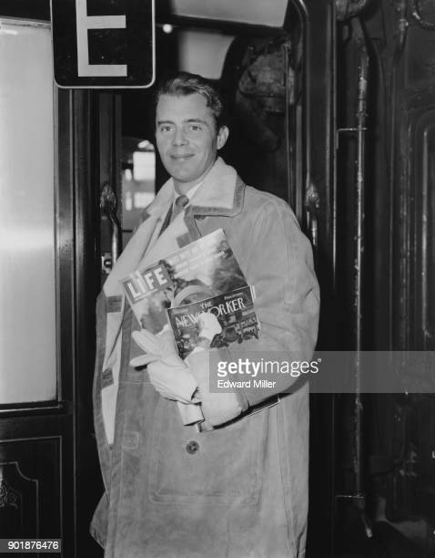 English actor Dirk Bogarde leaves Waterloo Station in London on the 'Queen Elizabeth' boat train carrying copies of 'Life' magazine and 'The New...