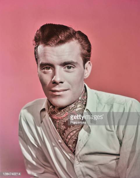 English actor Dirk Bogarde posed wearing a paisley pattern cravat under his shirt at his home in London in July 1949. Dirk Bogarde plays the role of...