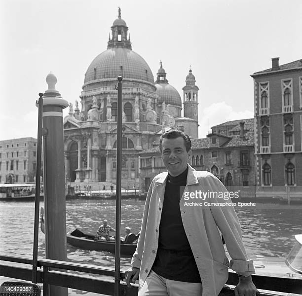 English actor Dirk Bogarde posing for the photographer along the Canal Grande the Salute in the background Venice 1960s
