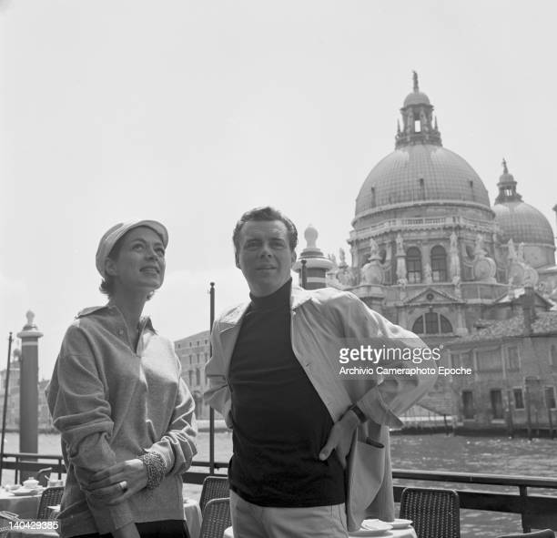 English actor Dirk Bogarde posing for the photographer with Jill Melford along the Canal Grande the Salute in the background Venice 1960s