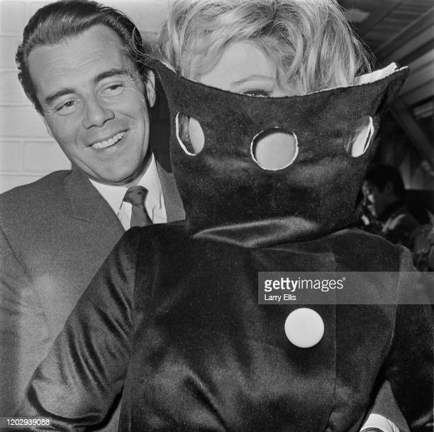 English actor Dirk Bogarde standing with Italian actress Monica Vitti as they attend a press call for the film 'Modesty Blaise' in London on 9th July...