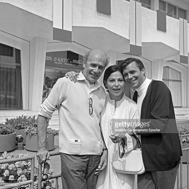 English actor Dirk Bogarde with movie director Jack Clayton and Israeli actress Haya Harareet outside the Movie Festival palace Lido Venice 1967