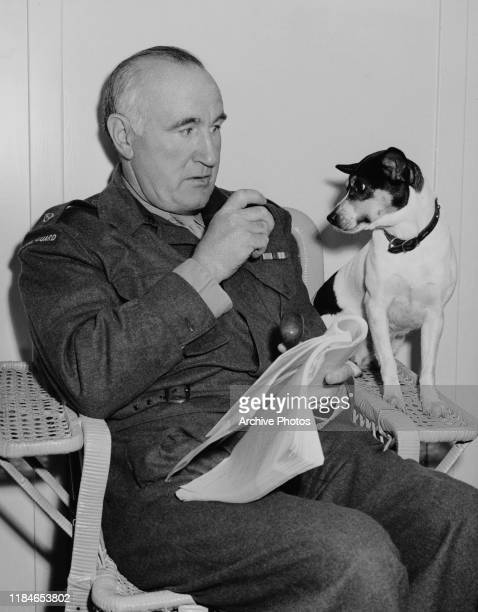 English actor Donald Crisp with his little terrier Velvet on the set of the film 'Son of Lassie', circa 1945. Crisp adopted Velvet during the filming...