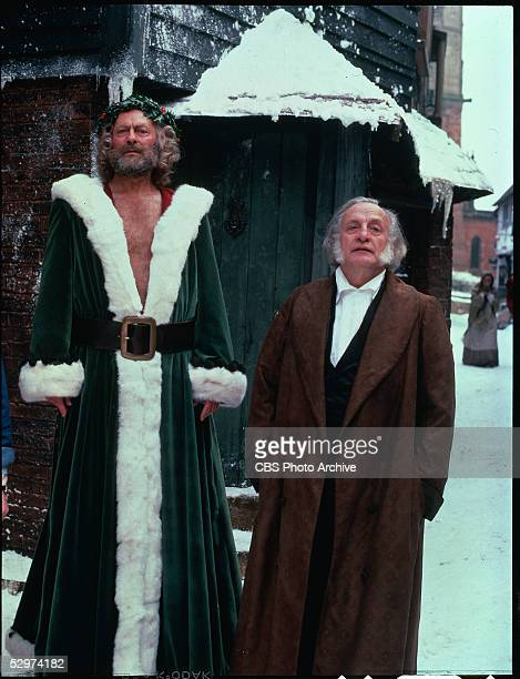 English actor Edward Woodward as Christmas Present and American actor George C Scott as Ebenezer Scrooge in a television adaptation of the 1843...