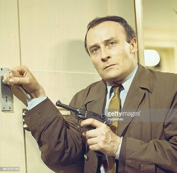 English actor Edward Woodward pictured holding a gun in one hand while opening a door in a scene from the television spy drama series 'Callan' in...