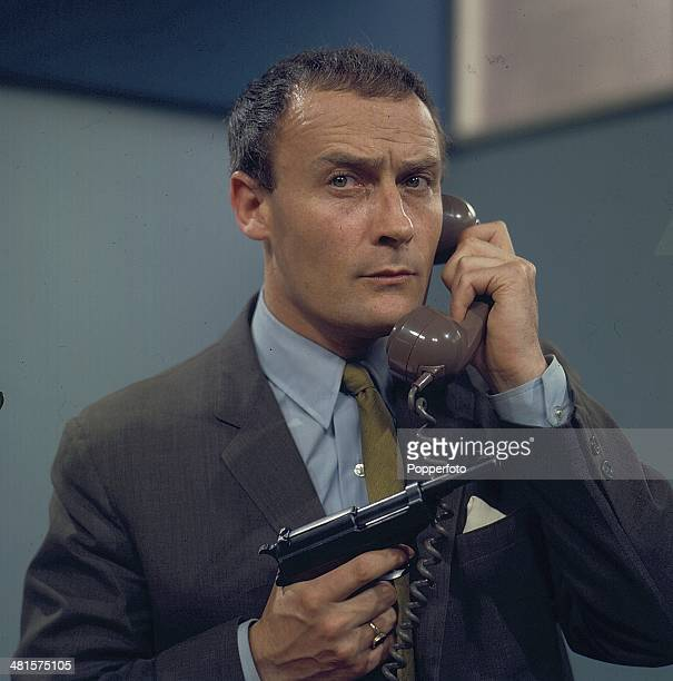 English actor Edward Woodward pictured holding a gun in one hand and a telephone in the other hand in a scene from the television spy drama series...