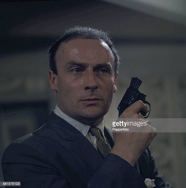 English actor Edward Woodward pictured holding a revolver in a scene from the television spy drama series 'Callan' in 1968.