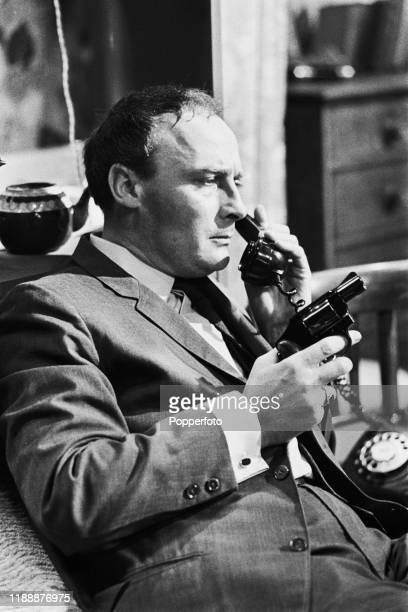English actor Edward Woodward, playing the role of David Callan, points a revolver in a scene from the ABC Weekend Television drama series 'Armchair...