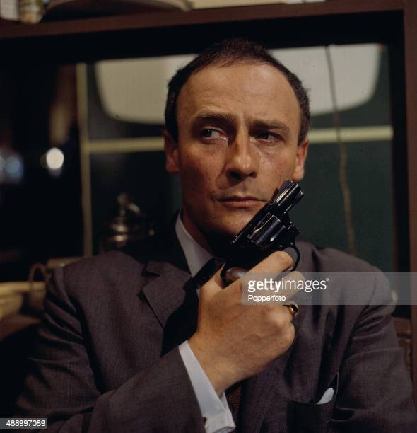 English actor Edward Woodward posed holding a gun in a scene from the television drama 'A Magnum For Schneider' in 1967.