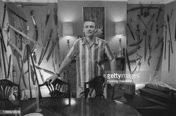 English actor Edward Woodward with a large collection of weapons, UK, July 1971.