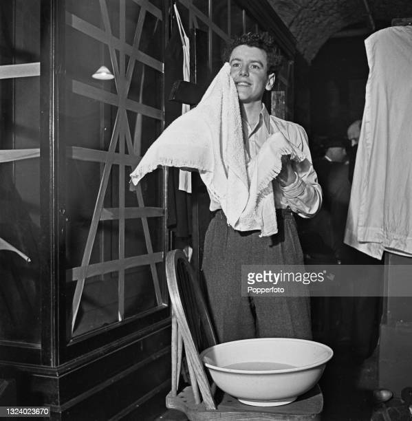 English actor George Cole has a wash after taking part in a performance of the Wyndhams comedy thriller 'Cottage to Let' to an audience of soldiers...