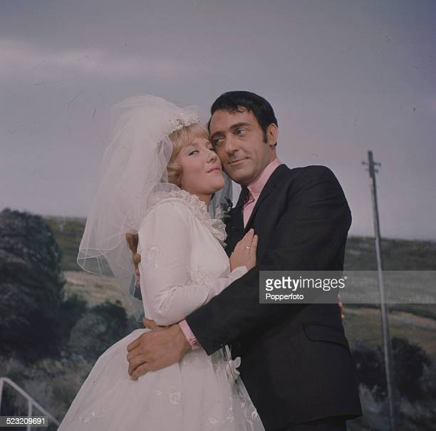 English actor Harry H Corbett pictured with actress Julia Foster dressed in a wedding dress and veil on the set of the film The Bargee in 1963